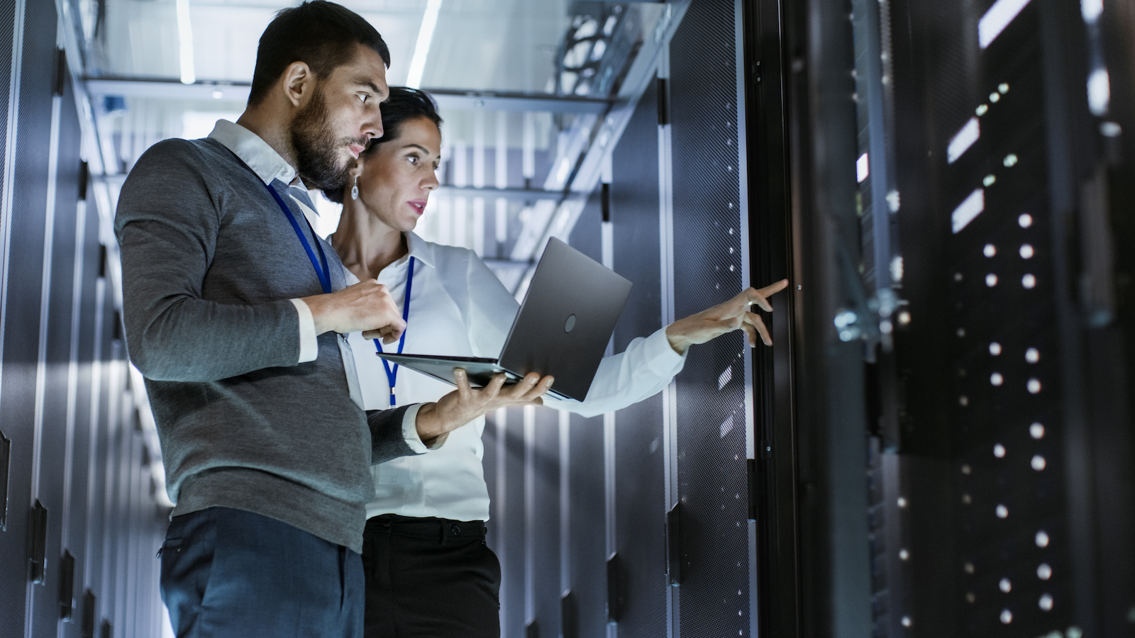 stock-photo-male-it-specialist-holds-laptop-and-discusses-work-with-female-server-technician-they-re-standing  1600-1